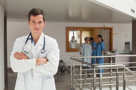 Smiling doctor standing in the hallway of a hospital while crossing his arms photo