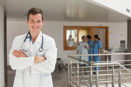 Laughing doctor standing in the hallway while crossing his arms photo