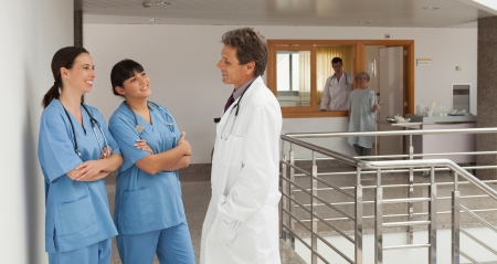 Doctor and two nurses, standing in the hall of a hospital while talking and having fun Stock Photo - 15591406