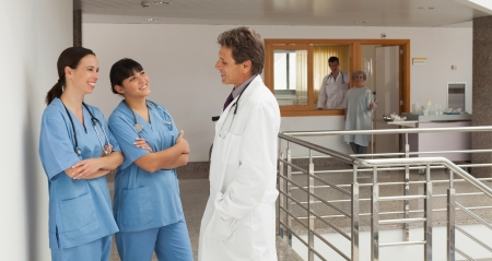 Three doctors standing in the hallway of a hospital while discoursing photo