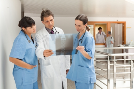 nurses station: Three doctors standing in a hospital while looking at a xray