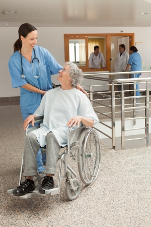 Nurse smiling at old women sitting in wheelchair in hospital corridor photo
