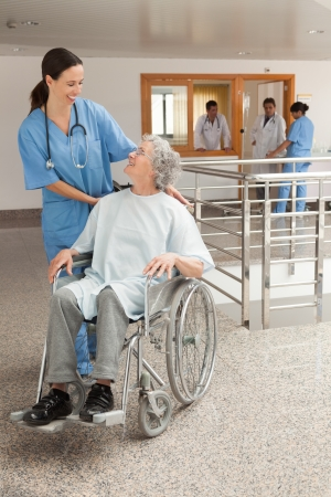 Nurse laughing with old women sitting in wheelchair in hospital corridor photo