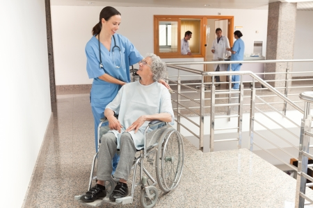 Nurse watching over old women sitting in wheelchair in hallway photo
