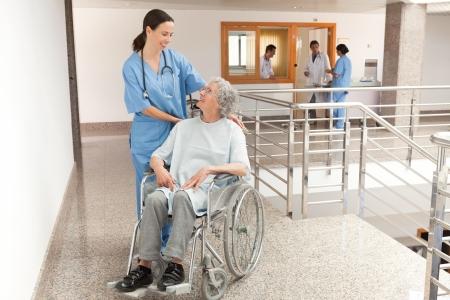 Nurse watching over old women sitting in wheelchair in hallway Stock Photo - 15593443