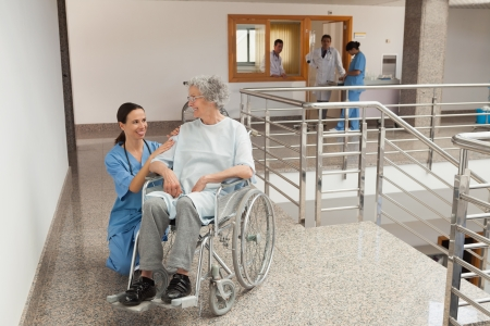 Nurse smiling and kneeling beside old women sitting in wheelchair  photo