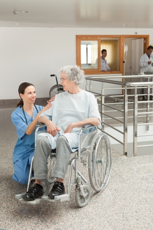 Nurse looking after old women sitting in wheelchair in hospital corridor photo