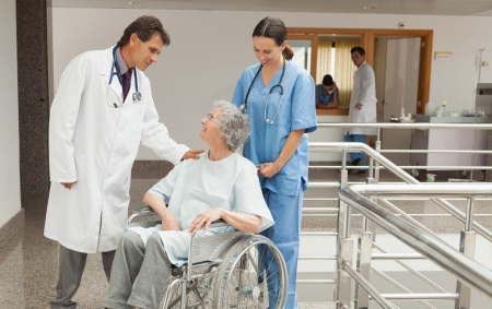 Nurse and doctor talking with old woman sitting in wheelchair in hospital corridor Stock Photo - 15584063