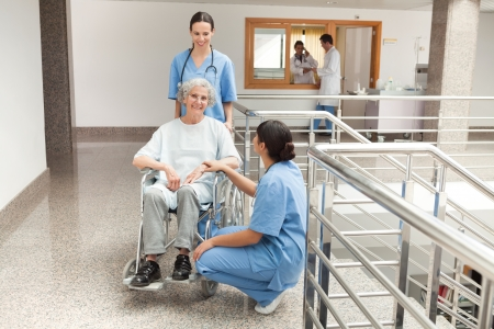Two nurses looking after old women sitting in wheelchair and holding her hand photo