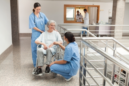 Two nurses talking with old women sitting in wheelchair and smiling photo