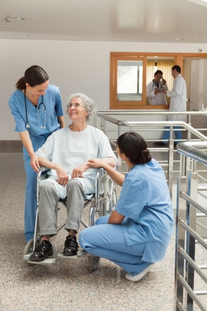 Old woman in wheelchair talking with nurses in hospital corridor