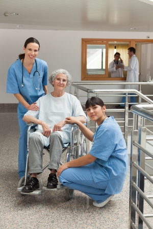 Two nursed with old woman in wheelchair in hospital corridor Stock Photo - 15593215