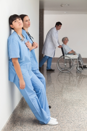 Two nurses leaning on wall with doctor pushing patient in wheelchair Stock Photo - 15593204