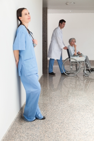 Nurse leaning against wall with doctor pushing patient in wheelchair photo
