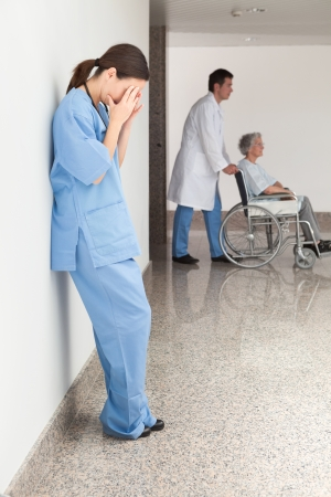 Stressed nurse leaning against wall with doctor pushing patient in wheelchair photo