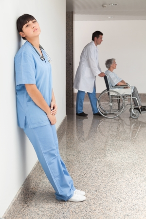 Tired nurse leaning against wall while doctor pushes patient in wheelchair photo