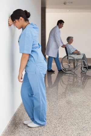 Distressed nurse standing against wall while doctor pushes patient on wheelchair photo