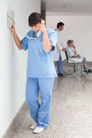 Nurse on telephone in hallway while doctor pushes patient in wheelchair Stock Photo - 15592748