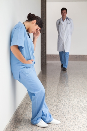 nurse station: Sad urse leans against wall in hospital corridor with doctor approaching