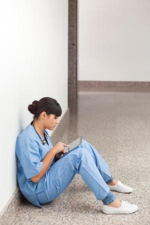 solicitous: Nurse using computer tablet in hospita corridor