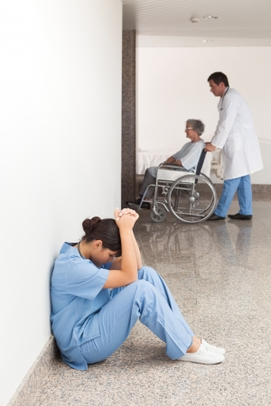 Nurse sitting on the ground in the hallway getting depressed Stock Photo - 15591988