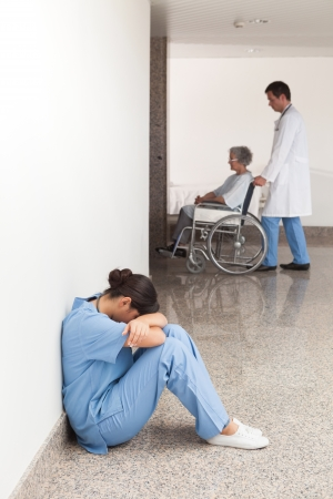 Nurse sitting on the ground in the hallway of the hospital with head in hands Stock Photo - 15592314