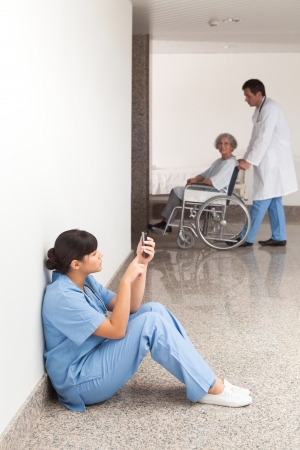 Nurse looking at her mobile phone while sitting in the hallway photo