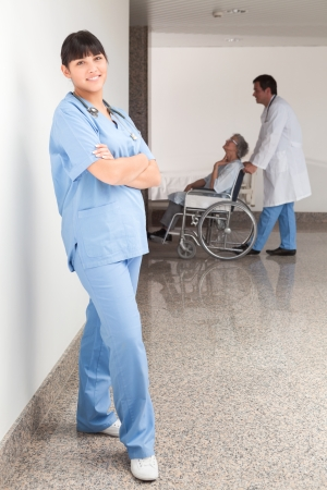 Proud nurse standing in hospital corridor photo