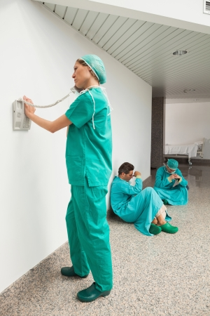 Surgeon using the phone in hospital corridor with two surgeons sitting on floor photo