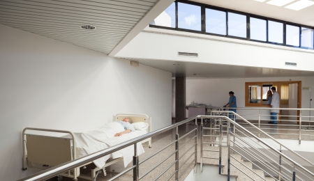 keep watch over: Patient lying in bed in hospital corridor