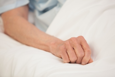 keep watch over: Elderly arm outstretched in hospital bed Stock Photo