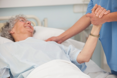 heal care: Elderly pateint in hospital bed holding hand of nurse Stock Photo