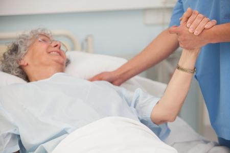atender: Pateint mayor en cama de hospital de la mano de la enfermera Foto de archivo