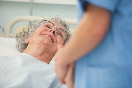 Elderly female patient looking up at nurse from hospital bed photo