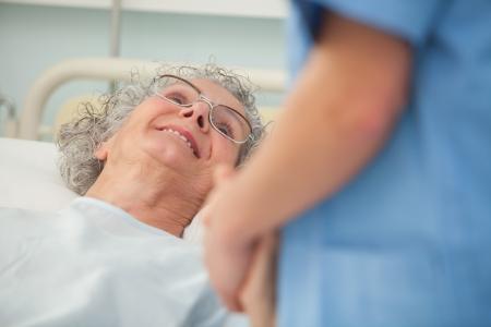 atender: Paciente Hembra mayor mirando a la enfermera de la cama de hospital