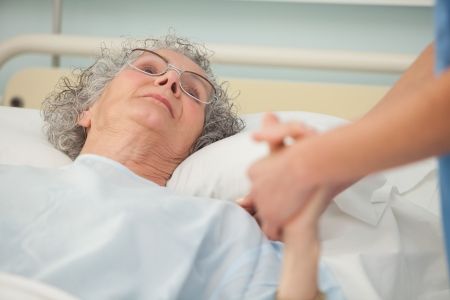 to attend: Nurse caring about old woman lying in bed Stock Photo