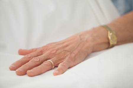 Hand of an old woman with golden jewelry in hospital bed photo