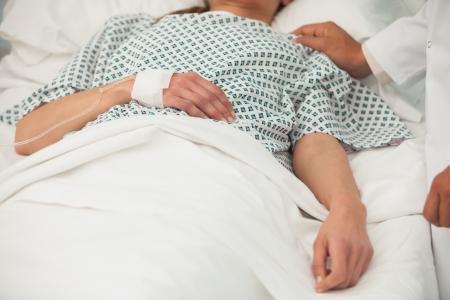 Una anciana enferma que miente en cama de hospital Foto de archivo