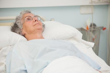 recuperation: Old sick lady lying in hospital bed