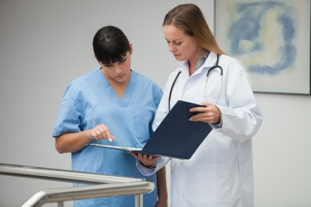 practitioner: Female doctor explaining notes to nurse and pointing in hospital corridor