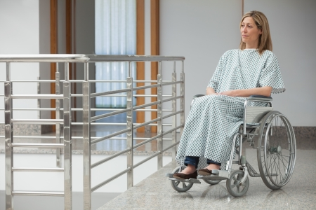 paraplegic: Woman wearing hospital gown and sitting in wheelchair in hospital corridor