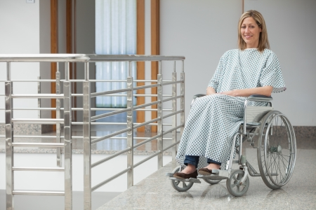 Smiling woman wearing hospital gown sitting in wheelchair in hospital corridor photo