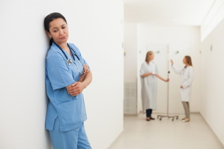 Nurse feeling sad with doctor talking to patient in hospital corridor photo