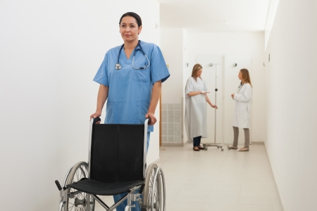 Nurse pushing empty wheelchair with doctor and patient talking in hospital corridor photo