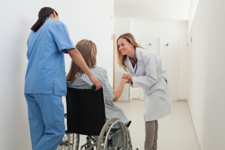 Doctor talking to patient in wheelchair while nurse is pushing in hospital corridor Stock Photo - 15591219