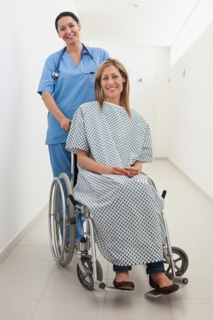 Happy nurse and patient in wheelchair in hospital corridor photo