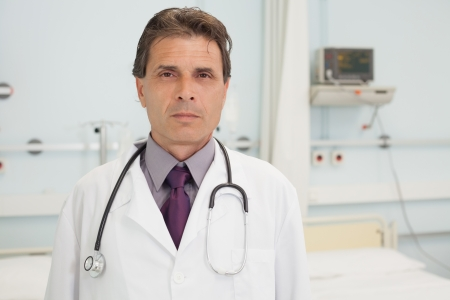 tend: Serious doctor standing in hospital bedroom Stock Photo