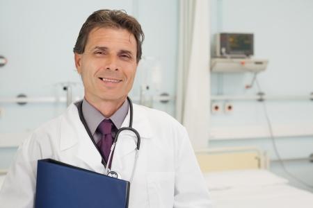 tend: Smiling doctor holding a folder in hospital bedroom