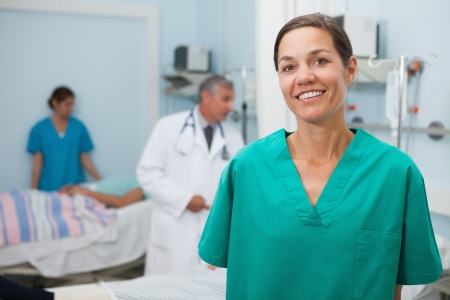 Nurse is standing in hospital room with doctor and other nurse in background Stock Photo - 15591490