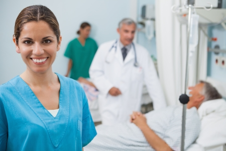 Happy nurse in hospital room with doctor, patient and other nurse in background photo